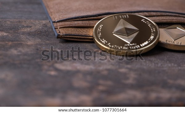 Ethereum coin with leather wallet on old wooden table top