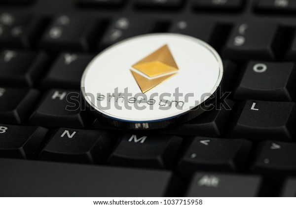 Ethereum crypto currency silver and gold coin lying on a black PC computer keyboard