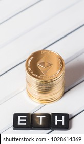 Ethereum cryptocurrency coin with ETH text on white wooden table top