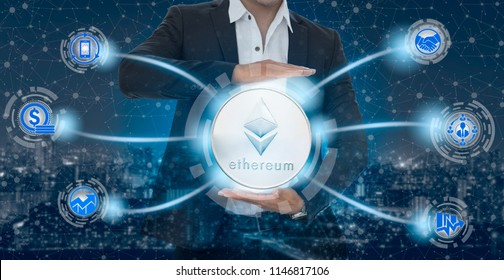 Ethereum and cryptocurrency investing concept - Businessman holding Ethereum (ETH) with mobile application business icons showing exchanging, trading, transfer and investment of blockchain technology.