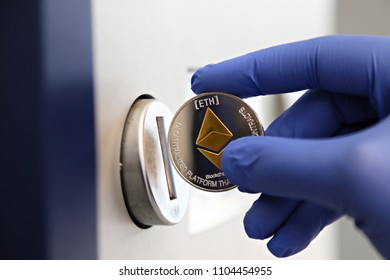 Ethereum cryptocurrency payments. Hand in a blue glove putting silver ethereum coin into a coin slot, shallow focus