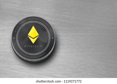 Ethereum (ETH) digital crypto currency. Stack of black and silver ether coins on table. Cyber money.