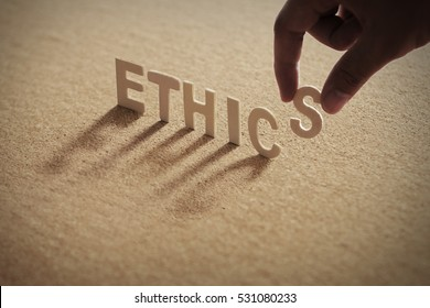 ETHICS wood word on compressed board with human's finger at S letter
