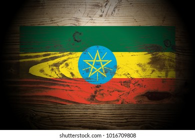 Ethiopia flag painted on dark_gold_and_brown_wood texture background