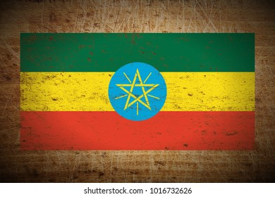 Ethiopia flag painted on scratched_wooden_board texture background