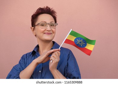 Ethiopia flag. Woman holding Ethiopian flag. Nice portrait of middle aged lady 40 50 years old with a national flag over pink wall background outdoors.