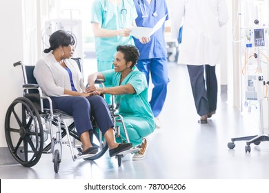 Ethnic African American female wheelchair patient with professional specialist nursing staff in corridor of hospital recovery center