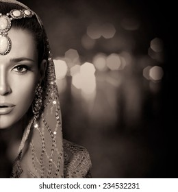 Ethnic Beauty Fashion. Beautiful hindu woman with traditional clothes, jewelry and makeup. Monochrome half face portrait with copy space for text