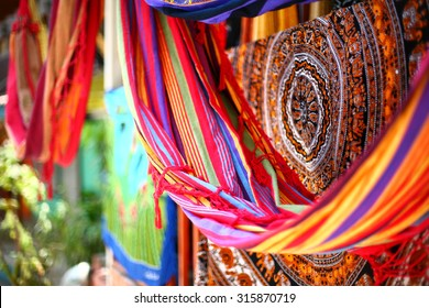 Ethnic blankets and hammocks with aztec various pattern hanging in street market