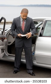 Ethnic Business Man with Clipboard and Pen next to Luxury Car working at the lake.