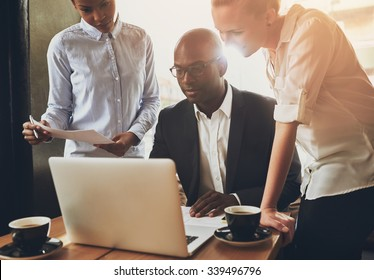 Ethnic business people, entrepreneurs working together using a laptop