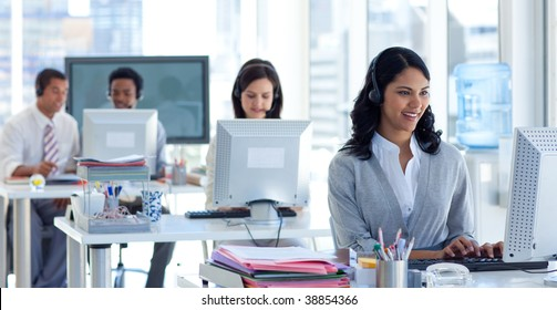 Ethnic businesswoman with a headset on in a call center with her colleagues