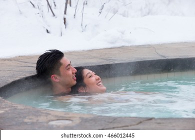 An ethnic couple visits an outdoor spa during Canadian winter
