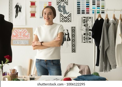 Ethnic embroidered clothing fashion designer standing at workplace  in studio with arms crossed looking at camera, talented young tailor shop owner posing at work desk, craftswoman in sewing workshop
