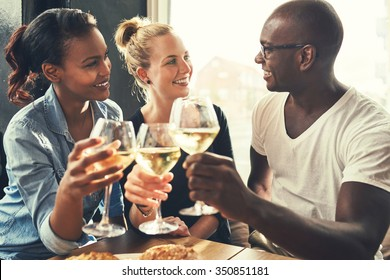 Ethnic friends at a bar drinking wine and eating tapas