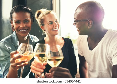 Ethnic friends drinking wine at a bar having a good time laughing