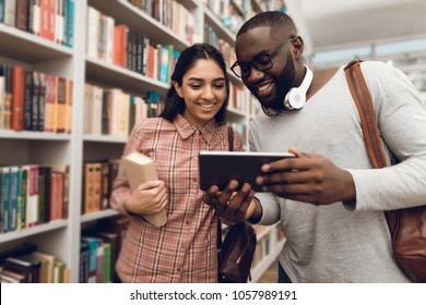 Ethnic indian mixed race girl and black guy surrounded by books in library. Students are using tablet.