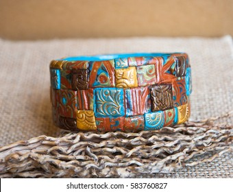 Ethnic jewellery bracelet on rustic fabric. Handmade jewelry bracelet of polymer clay.Fashion background with bangle bracelet.Hobby, handicraft.