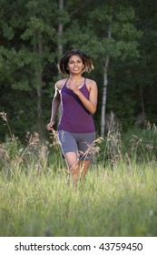 An ethnic looking woman in her 20's running