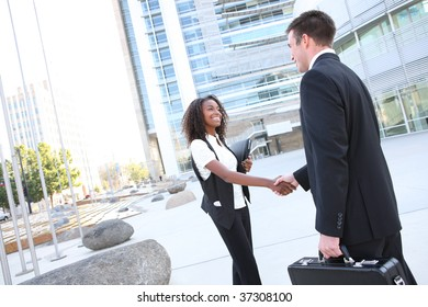 Ethnic Man and Woman Business Team shaking hands at office building