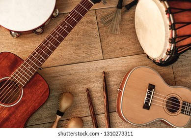 Ethnic musical instruments set: tambourine, wooden drum, brushes, wooden sticks, maracas and guitars laying on wooden floor. Music concept. Musical instruments.