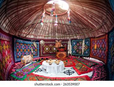 Ethnic nomadic house yurt interior with table of national food at Nauryz celebration
