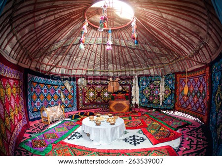 Ethnic nomadic house yurt interior with table of national food at Nauryz celebration