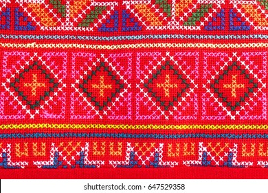 Ethnic pattern. Classic pattern from hill tribe embroidery. pattern in native hill tribe style in Magenta pink and red on coin purse or smartphone purse, popular souvenir texture surface