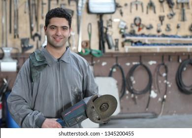 Ethnic worker holding esmeril angular tool