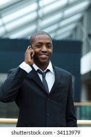 Ethnic young businessman speaking on phone and smiling at the camera