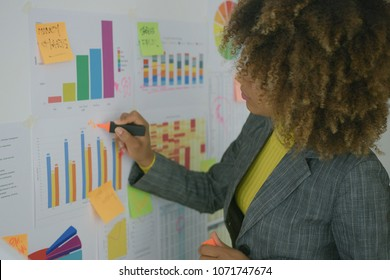 Ethnic young model in elegant suit using pen and drawing on paper with colorful charts presenting new data while working in office.