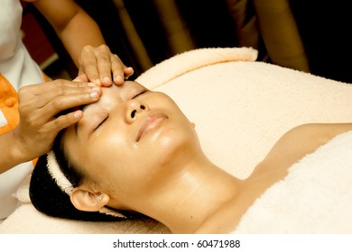 Ethnic young woman having face massage at beauty clinic