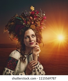 Ethno Beauty. Beautiful young woman in traditional ukrainian crown posing on the summer field