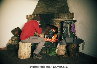 ETNA PARK, SICILY, ITALY - NOVEMBER 02, 2018: hiker drinking and sitting in front of fireplace in a mountain refuge