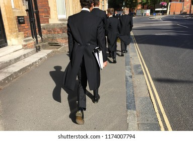 Etonian schoolboys, from the English independent boarding school, Eton College, dressed in traditional uniform of tails, going to class in the famous, historic town of Eton in Windsor, England