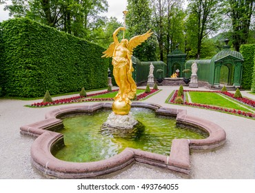 ETTAL, GERMANY - JUNE 5, 2016: Sculpture of gold angel in the park of Linderhof Palace, Bavaria, Germany.