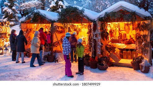 Ettal, Germany/Bavaria – December 31, 2019: Snowy Christmas market with illuminated shops in wooden huts with gifts and handmade decoration.