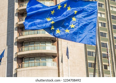 EU flag waving in the wind with building in background