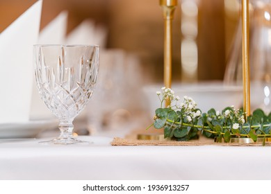 Eucalyptus with glass and candles on white table