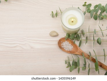Eucalyptus leaves and candle and,salt in spoon,stones on wooden background