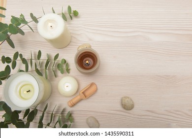 Eucalyptus leaves and candle and,spoon,stones on wooden background