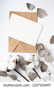 Eucalyptus leaves and cotton flowers  on white background. Flat lay, top view. craft envelope. card mockup