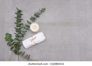 Eucalyptus leaves rolled towel, candle and on gray background