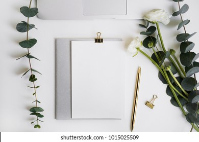 Eucalyptus and ranunculus flower, laptop keyboard, pen, grey copybook with paper mock-up on white table top view. Plants in home office. Feminine floral desktop.
