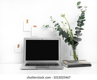 Eucalyptus and ranunculus flower, laptop screen, books and accessories on white table. Feminine home office. Minimal floral desktop with white wall.