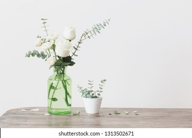 eucalyptus twigs and white roses  in  glass vase on white background