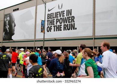 EUGENE, OR - APRIL 28, 2013: Start of the Eugene Marathon with runners running past a big Nike advertisement that says believe in the power of the run.
