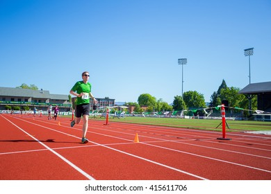 EUGENE, OR - MAY 1, 2016: Runner approaching the finish line on the track at Hayward Field during the 2016 Eugene Marathon, a Boston qualifying event.