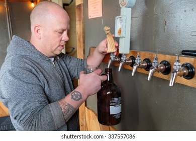 EUGENE, OR - NOVEMBER 4, 2015: Bartender and brewery co-owner Brandon Woodruff pouring Exalted IPA on tap at the startup craft brewery Mancave Brewing.