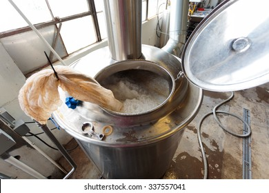 EUGENE, OR - NOVEMBER 4, 2015: Boiling all grain mash to create wort in the commercial brewing process at the startup craft brewery Mancave Brewing.